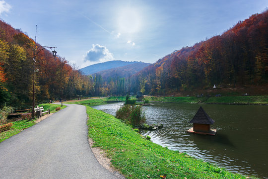 beautiful park in the mountains. wonderful sunny autumn weather. walking path around the pond. trees in fall foliage. lanterns and benches along the way, blue sky with clouds