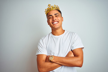 Young brazilian man wearing king crown standing over isolated white background happy face smiling...