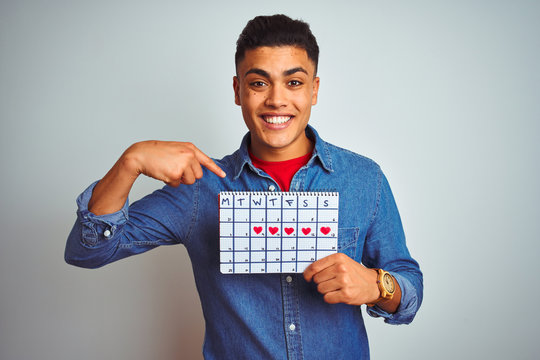 Young brazilian man holding calendar standing over isolated white background with surprise face pointing finger to himself