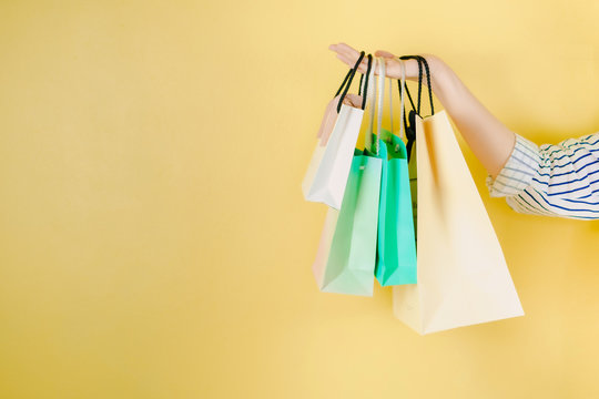 web banner mid season sale and shopping activity from hand hold the shopping bag with copy space and yellow vintage background