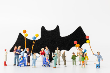 Miniature people:  Happy family holding balloon on white background Happy Halloween concept Wall mural