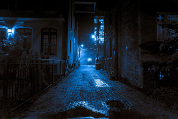 Dark and scary vintage cobblestone brick city alley at night in Chicago Wall mural