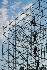 silhouettes of workers on scaffolding
