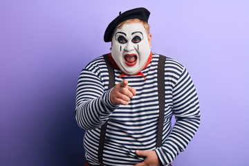 funny clown showing with index finger to the camera. close up photo. isolated blue background, studio shot. joke, fun, craziness, madness