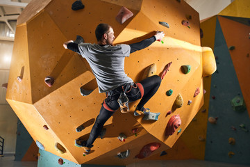 Full length back view of young physically challenged climber trying to reach top of difficult artificial climbing wall, wearing comfortable sportswear and shoes, harness and chalk bag on his waist.