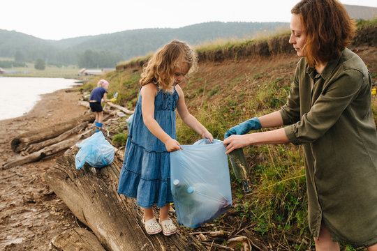 Mother with her daughters collecting bottles in garbage bags on a river shore