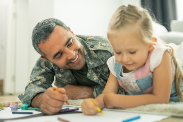 Daddy smiling while painting family tree with daughter