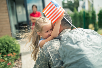 Daughter holding little American flag hugging daddy tight Fototapete