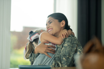 Military woman laughing while hugging her daughter