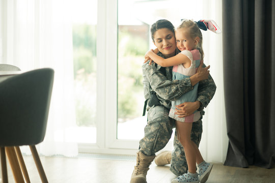Dark-haired military woman hugging cute blue-eyed daughter