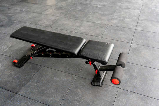 Black and red reinforced flat inclined weights bench. Bench for weight training with weights and dumbbells