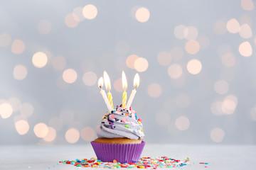 Tasty Birthday cupcake on table against defocused lights