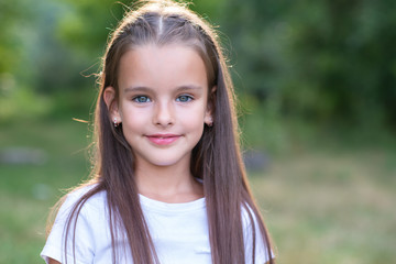 Pretty little girl with long brown hair posing summer nature outdoor. Kid's portrait. Beautiful child's face