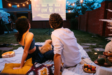 Couple in love watching a movie, in twilight, outside on the lawn in a courtyard Wall mural