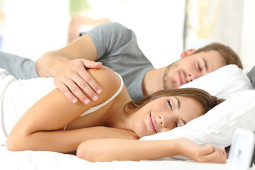 Couple sleeping together in a bed in the morning