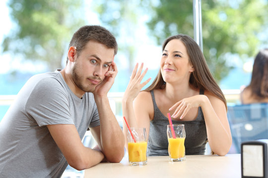 Bored man listening her friend talking in a bar