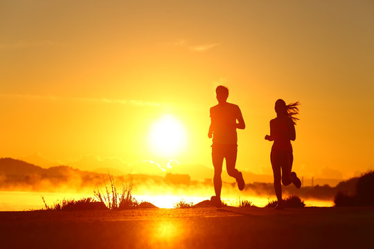 Couple shilouette running at sunrise on the beach