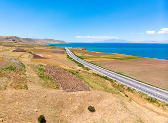 Aerial view of Lake Van the largest lake in Turkey, lies in the far east of that country in the provinces of Van and Bitlis. Fields and cliffs overlooking the crystal waters. Roads along the lake