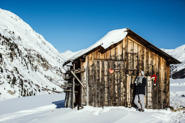 Mann mit Schal und Tasse mit Getränk vor Holzhütte erholt sich in den Alpen im Winter