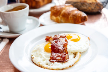 classical english breakfast with egg and croissants