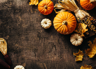 Autumn background with festive decoration, small pumpkins, decorative corn, maple leaves. Top view. Copy space.