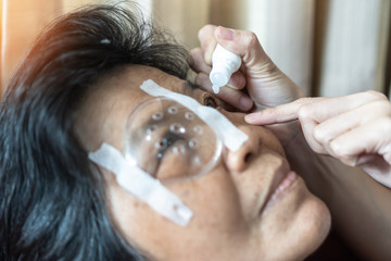 Elderly patient woman having eye drop care on Age-related eye diseases, AMD, Diabetic retinopathy, Glaucoma, low vision, dry eyes