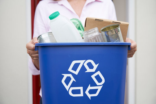 Close Up Of Woman Holding Recycling Bin Of Reusable Waste Outside Front Door