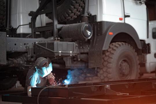 Welder in a car workshop welds a truck frame