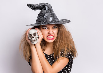 Happy halloween concept. Teen girl in witch black hat holding skull and baring her teeth with anger on grey background. Young teenager in witch halloween costume with spooking make-up. Wall mural