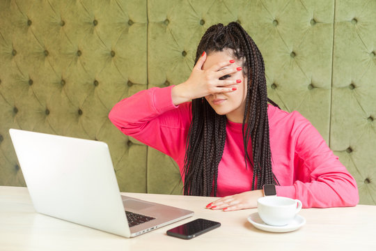 Portrait of emotional disbelief young woman with black dreadlocks hairstyle in pink blouse sitting in cafe and covering the eyes with hand, peeking cause don't want to see, looking at camera. Indoor