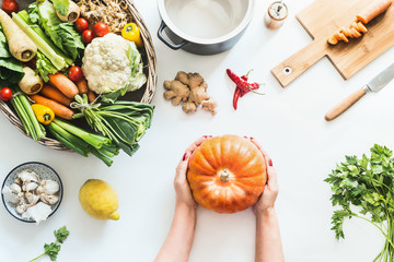Female girls hands holding pumpkin on white table background with various organic farm vegetables und pot, top view. Seasonal cooking. Healthy lifestyle. Autumn food.  Flat lay.  Low carb veggies