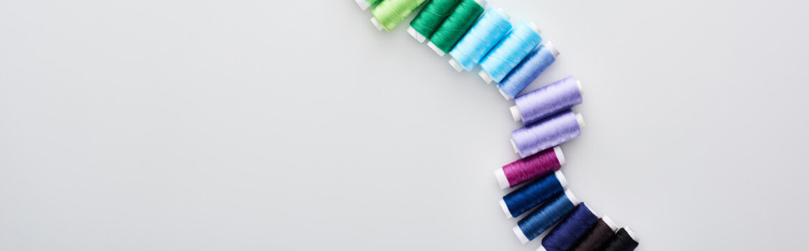 panoramic shot of bright and colorful threads on white background