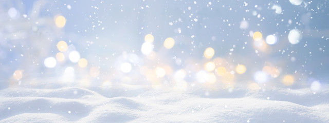 Festive Christmas natural snowy landscape, abstract empty stage, background with snow, snowdrift and defocused Christmas lights. Blue and yellow Golden Christmas lights against blue sky, copy space.