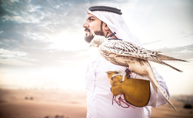 Deurstickers Abu Dhabi Arabic man with traditional emirates clothes walking in the desert with his falcon bird