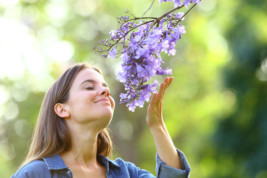 Candid woman smelling flowers in a park