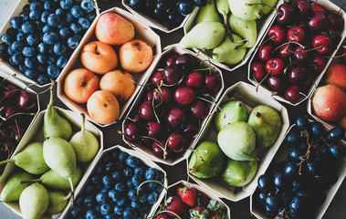 Summer fruit and berry variety. Flat-lay of ripe strawberries, cherries, grapes, blueberries, pears, apricots, figs in wooden eco-friendly boxes over grey background, top view. Local farmers produce