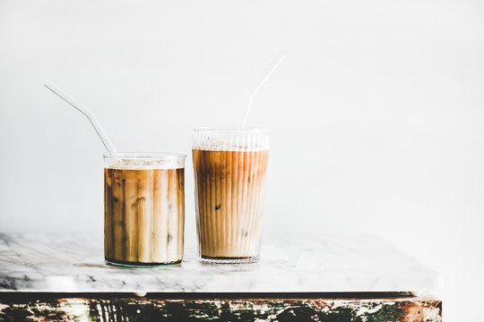 Homemade iced latte coffee in glasses with straws on grey marble table, white wall at background, copy space. Summer cold refreshing drink concept