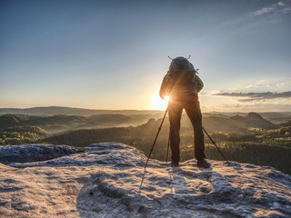 Artist set camera and tripod to photograph sunrise on summit