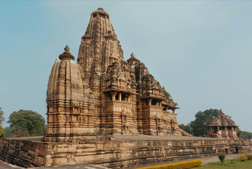 Famous Hindu temples in Khajuraho with reliefs and ancient sculptors on facades, India. Indian historical design and towers of the 10th century temples