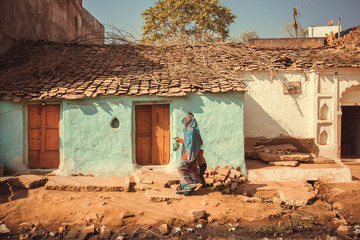 People walking past small traditional indian village house. Colorful buildings of rural area in India
