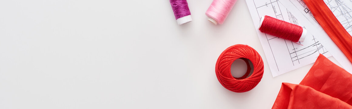 panoramic shot of colorful threads, knitting yarn ball, fabric, sewing patterns and zipper on white background