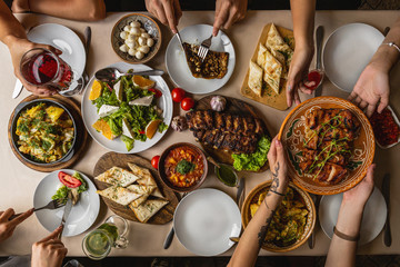 large and generously covered with delicious dishes table, covered with a tablecloth on which there are various delicious dishes of Ukrainian cuisine: fried ribs, borsch, salads, cheese