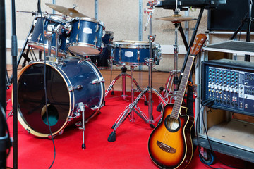 Set of musical instruments ready for rehearsal of music band in modern sound studio