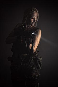 Art portrait woman with gun with flashlight in smoke