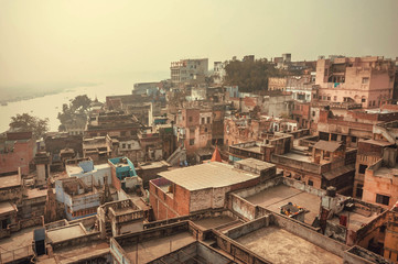 Buildings near Ganges river, historical cityscape of Varanasi, view over roofs of the poor brick houses, India