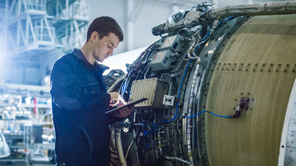 Aircraft Maintenance Mechanic Inspecting and Working on Airplane Jet Engine in Hangar Fototapete