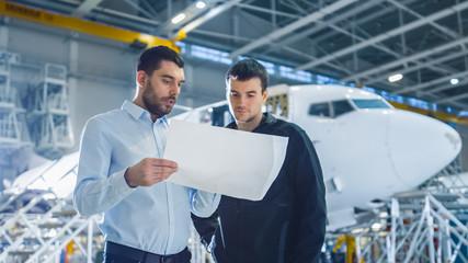 Aircraft Maintenance Worker and Engineer having Conversation. Holding Project Blueprint.