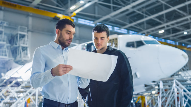 Aircraft Maintenance Worker and Engineer having Conversation. Holding Project Blueprint.