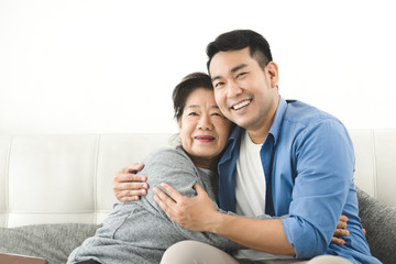 Asian mother hugging her son and sitting on sofa at home, lifestyle concept.