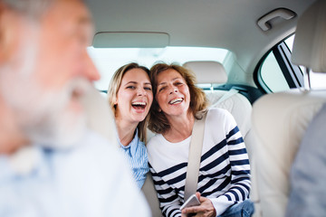Cheerful adults sitting in car, going on a trip.